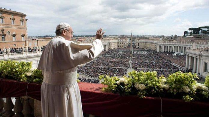 Paus Fransiskus menyapa umat sebelum menyampaikan pesan Paskah-nya dari balkon yang menghadap ke Lapangan Santo Petrus di Vatikan, 1 April 2018. Paus menyerukan perdamaian di Tanah Suci Yerusalem dua hari setelah 15 orang Palestina tewas di perbatasan Israel-Gaza. Osservatore Romano/REUTERS